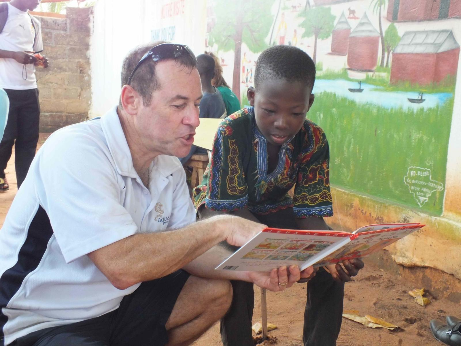 Voluntario mayor de 50 años ayudando a leer a un niño.